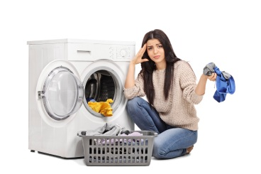 Sad woman emptying a washing machine