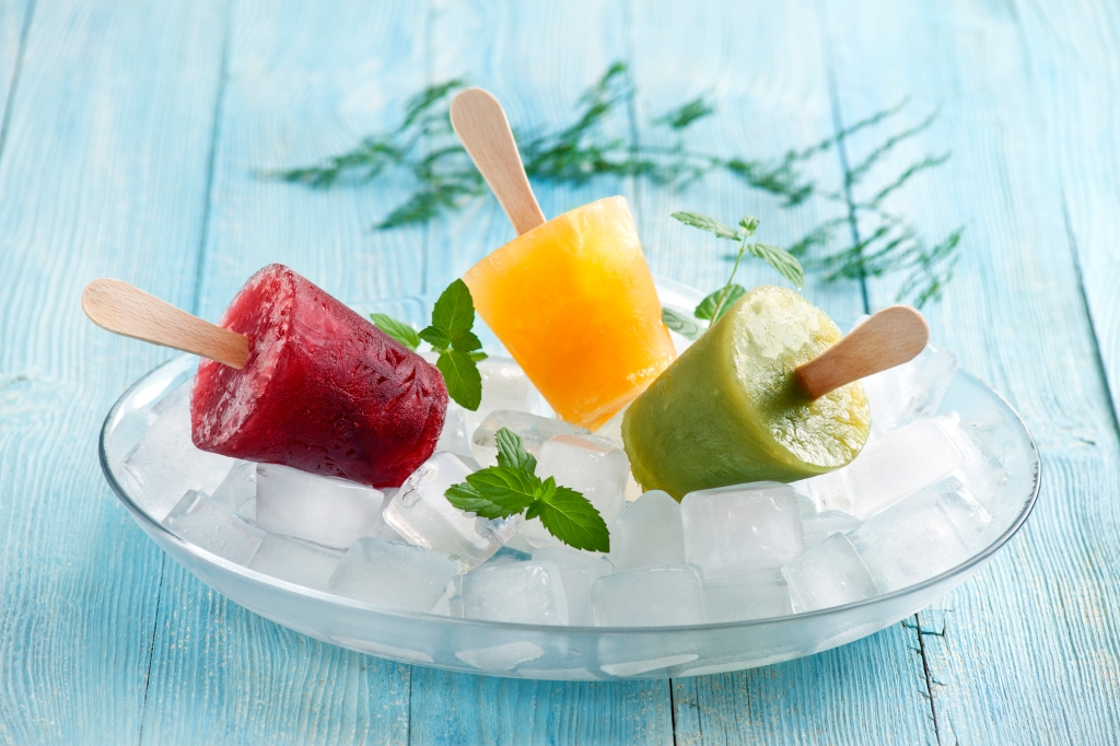 Homemade popsicles with ice cubes on wooden table