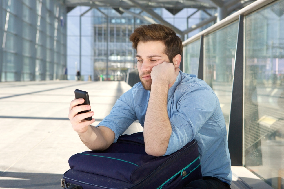 Man waiting at airport with bored expression on face
